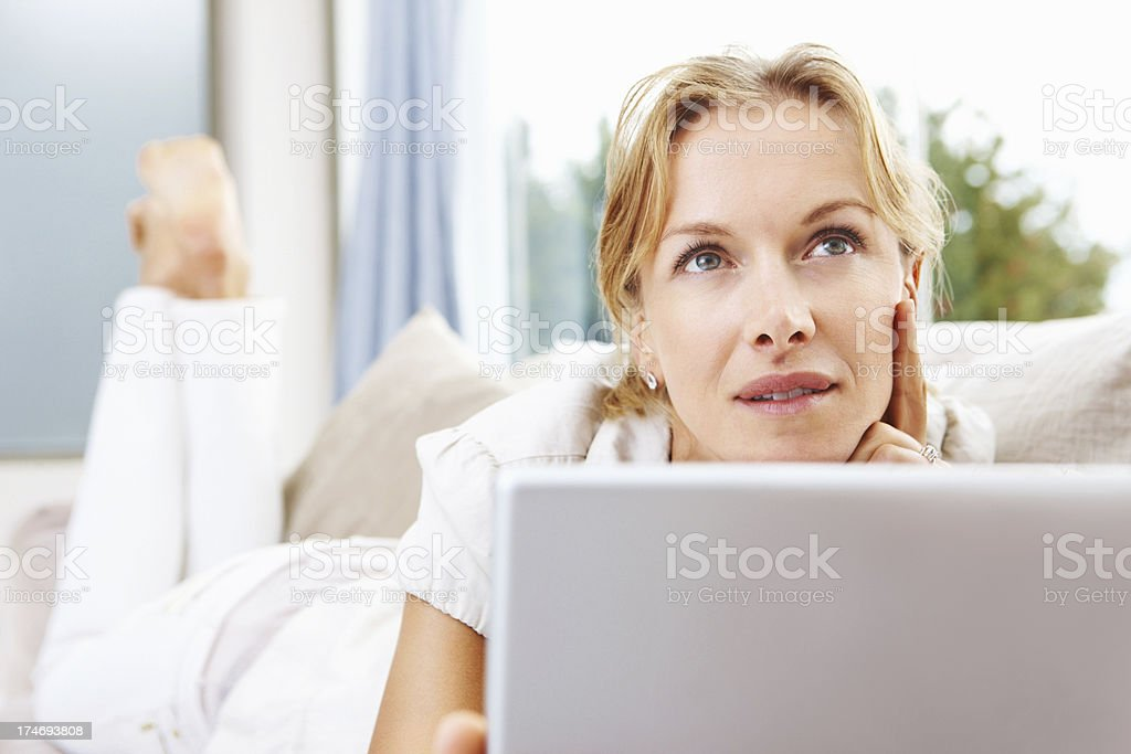 Mid adult woman using a laptop and thinking royalty-free stock photo