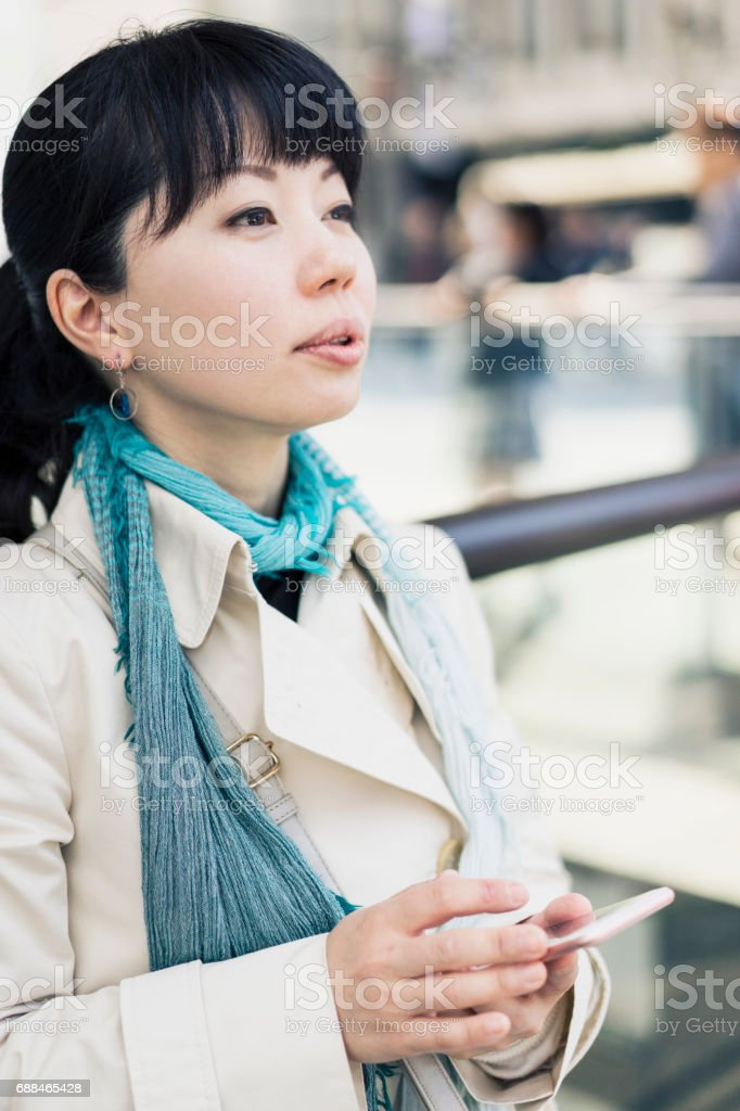 Mid adult woman using a smartphone in the city. stock photo