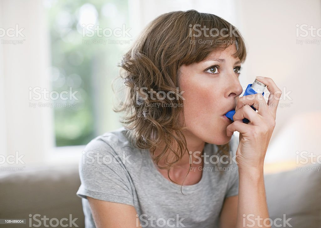 Mid adult woman using asthma inhaler stock photo
