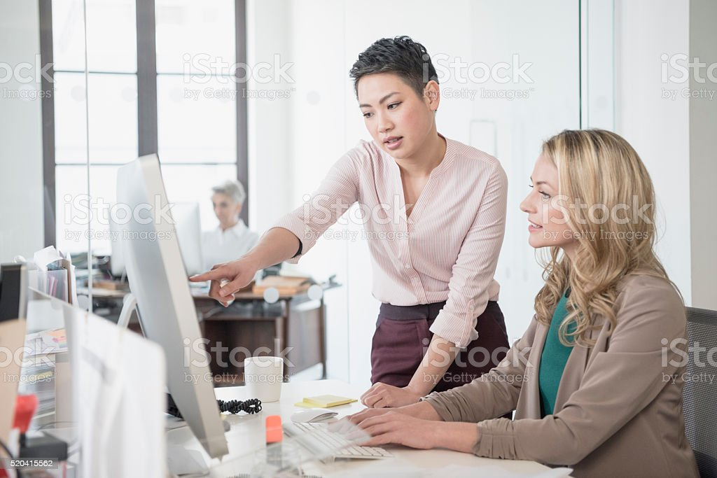 Mid adult woman using computer, young woman pointing stock photo