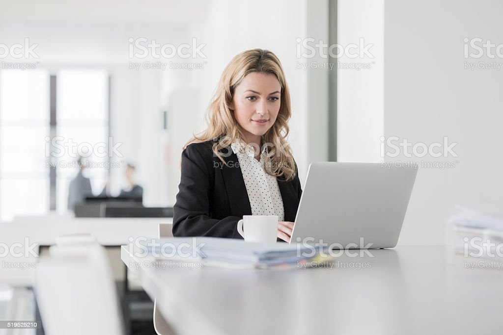 Mid adult woman using laptop and concentrating in office stock photo