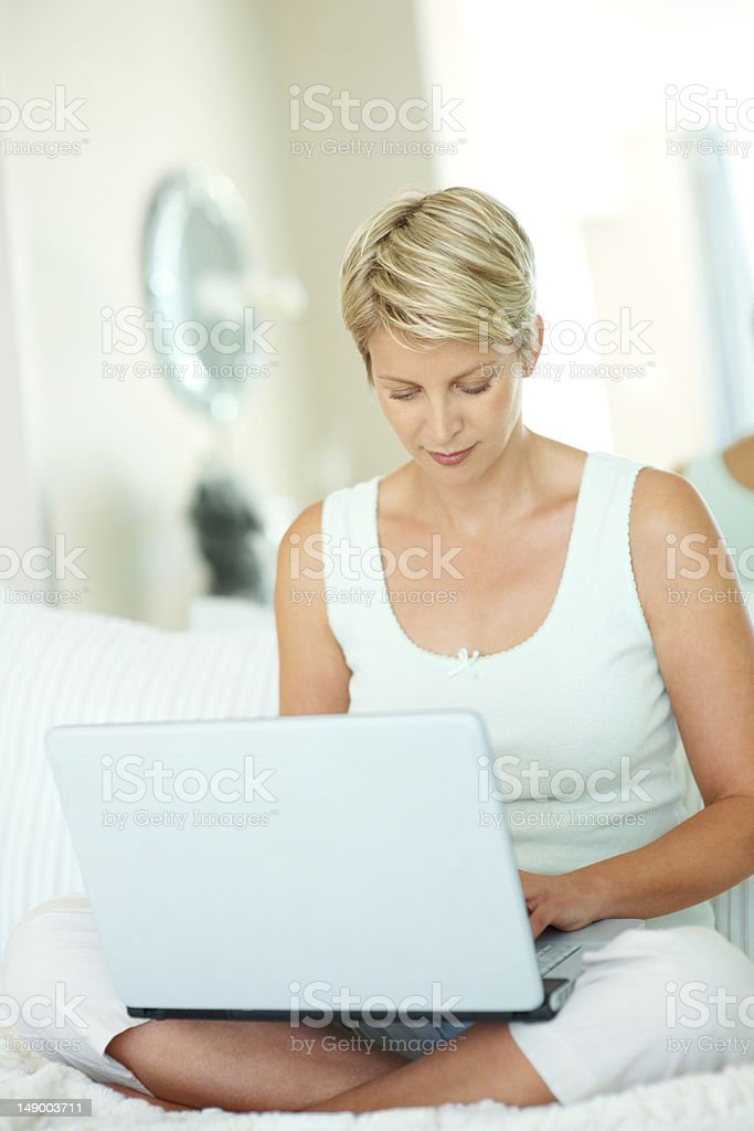 Mid adult woman using laptop while sitting in bed royalty-free stock photo