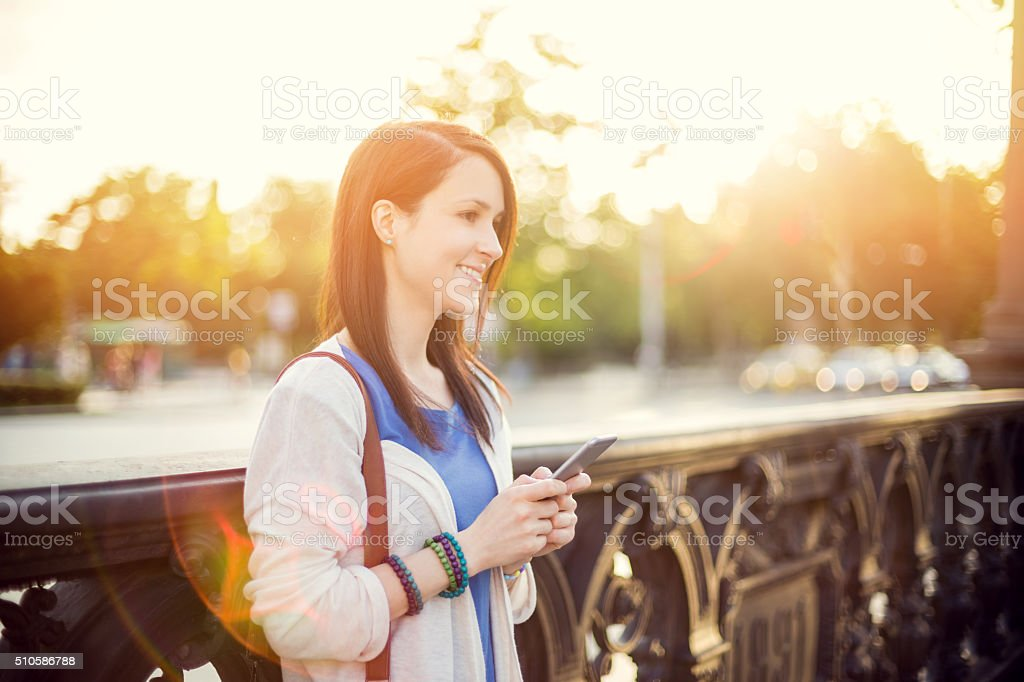 Mid adult woman using smartphone stock photo