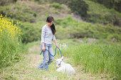Mid adult woman walking her pet goat at organic farm