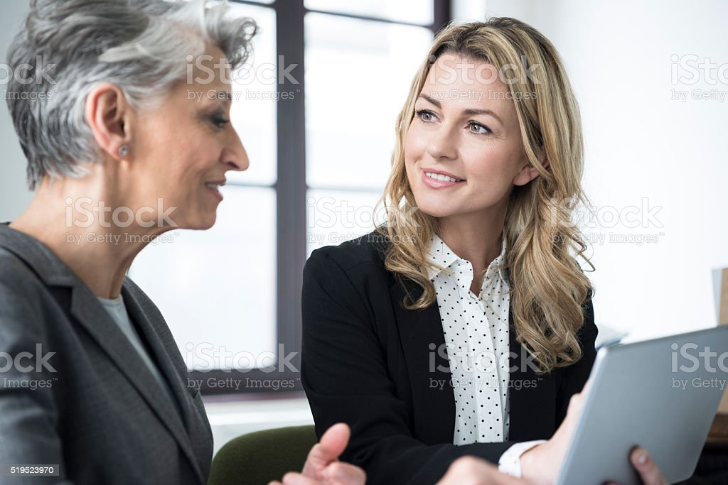 Mid adult woman with tablet smiling at mature colleague stock photo