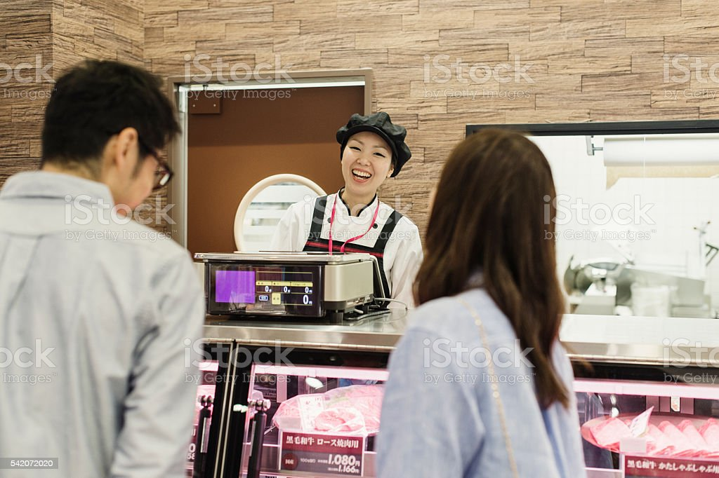 Mid adult woman working in the butcher. stock photo