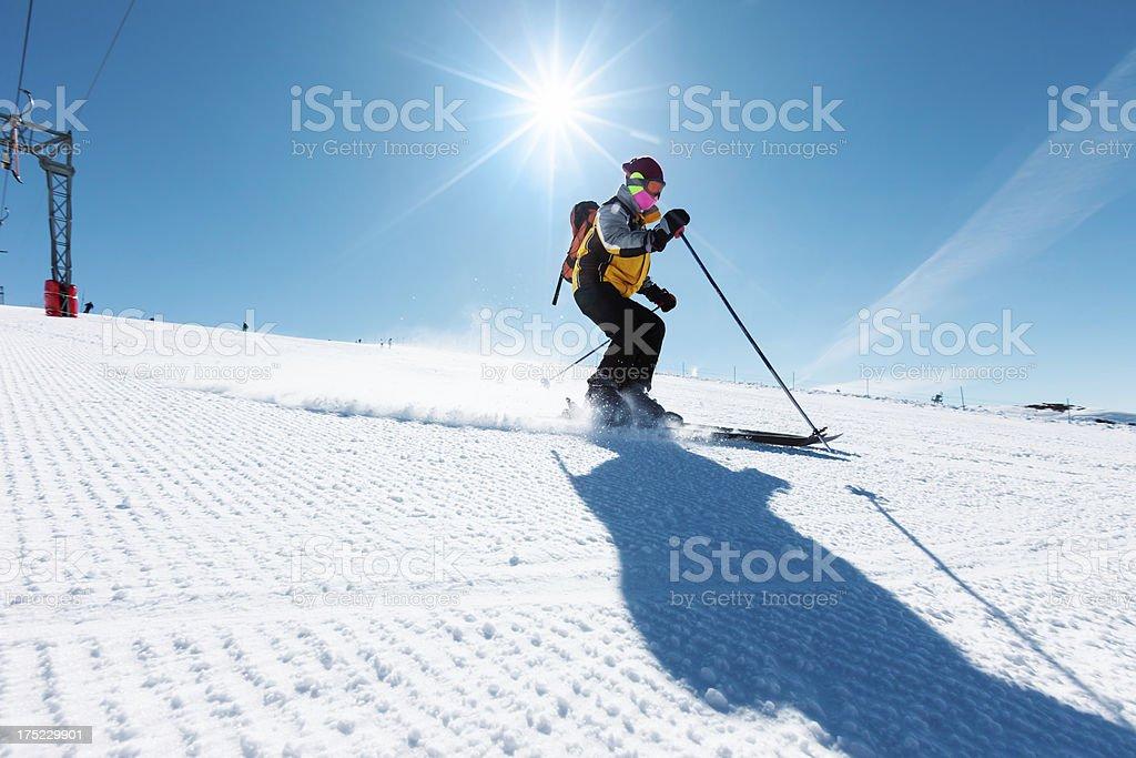 Mid adult women snow skier skiing on sunny ski resorts stock photo