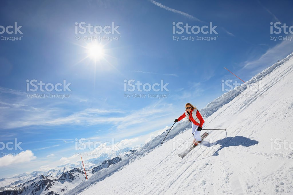 Mid adult women snow skier skiing on sunny ski resorts stock photo