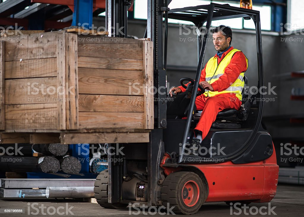 Mid adult worker driving forklift with palette in distribution warehouse. stock photo