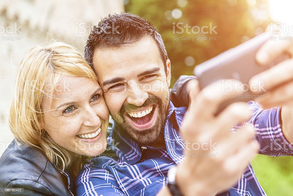 Mid Adults Couple Taking Pictures with a Smartphone royalty-free stock photo