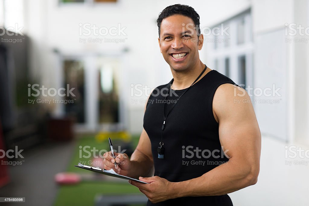 mid age trainer holding clipboard stock photo