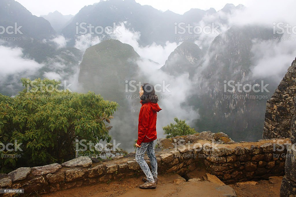 mid age woman in coat in Machu Picchu citadel, Peru stock photo