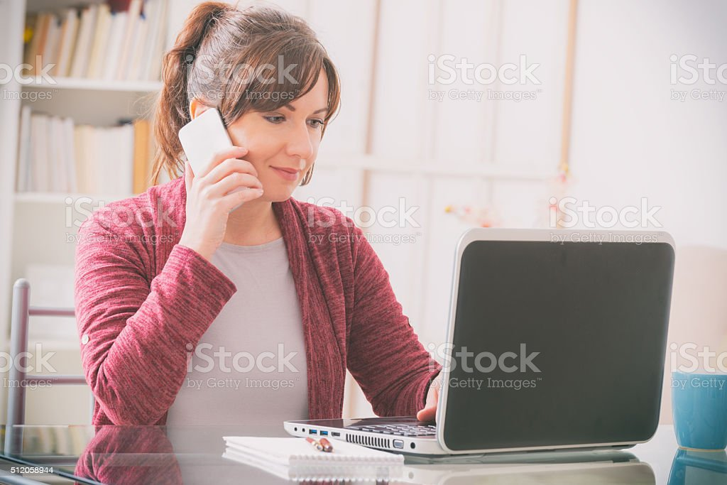 Mid age woman sitting at table stock photo