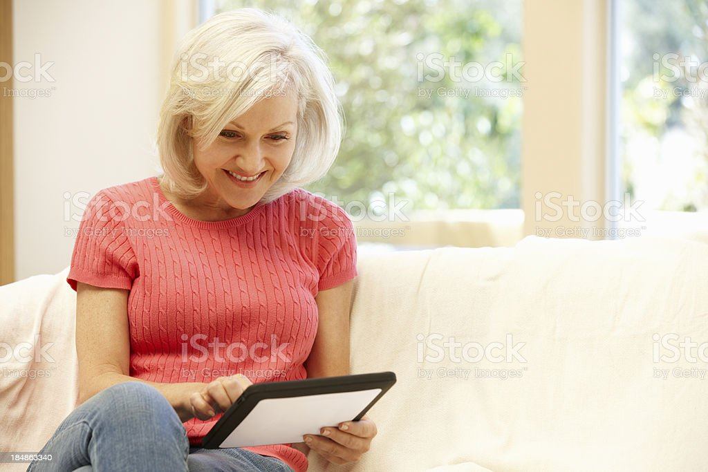 Mid age woman using tablet at home stock photo