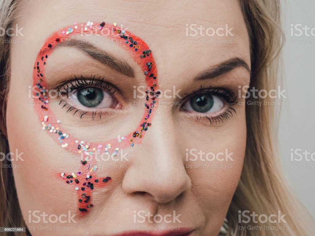 Mid age woman with feminism mark on her face stock photo