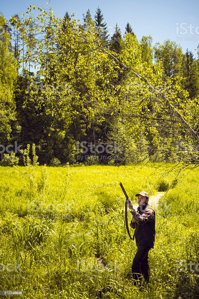 Mid Aged Man With A Gun Standing in a Marshland stock photo