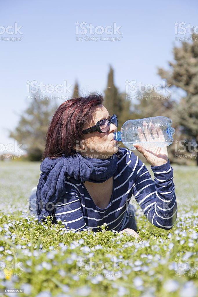 Mid aged woman relaxing and drinking water on grass royalty-free stock photo