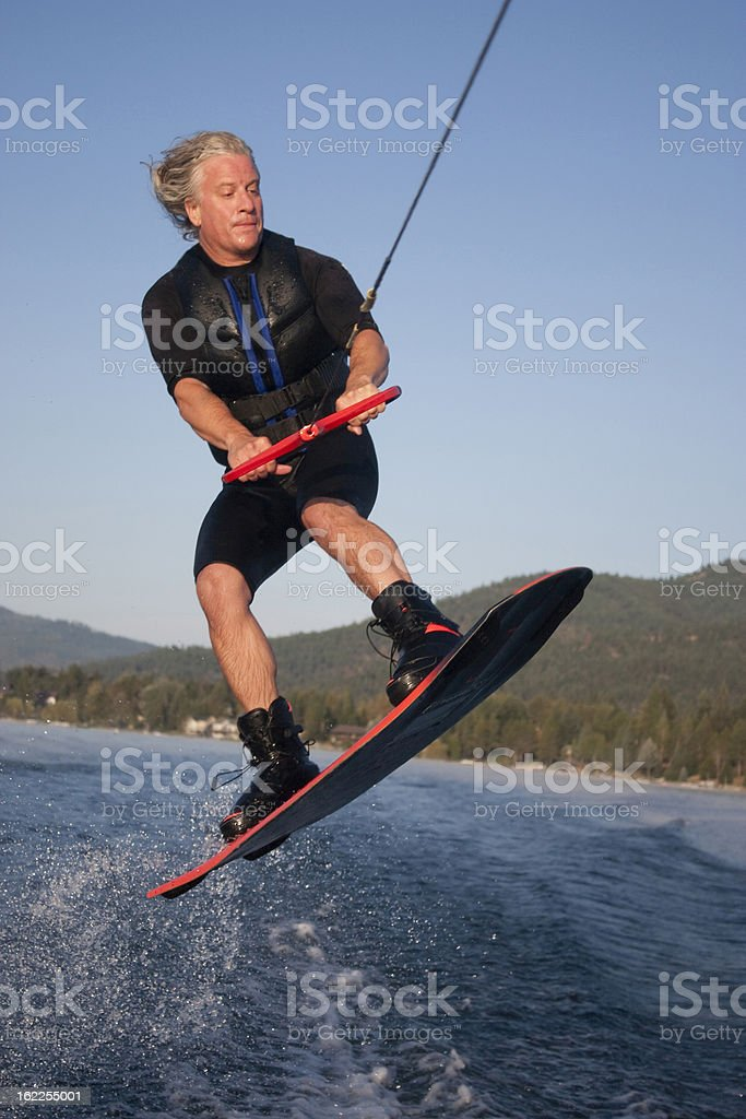 Mid forties male jumping on his wakeboard stock photo