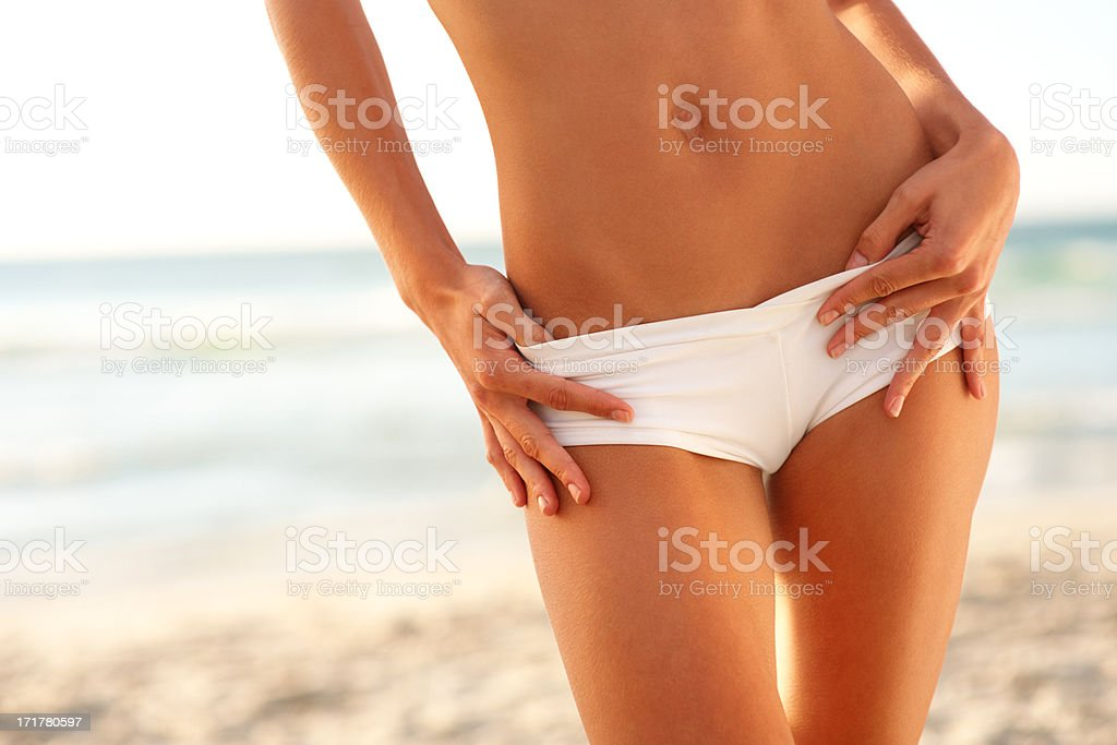 Mid section image of a woman in white bikini bottoms at the sea shore stock photo
