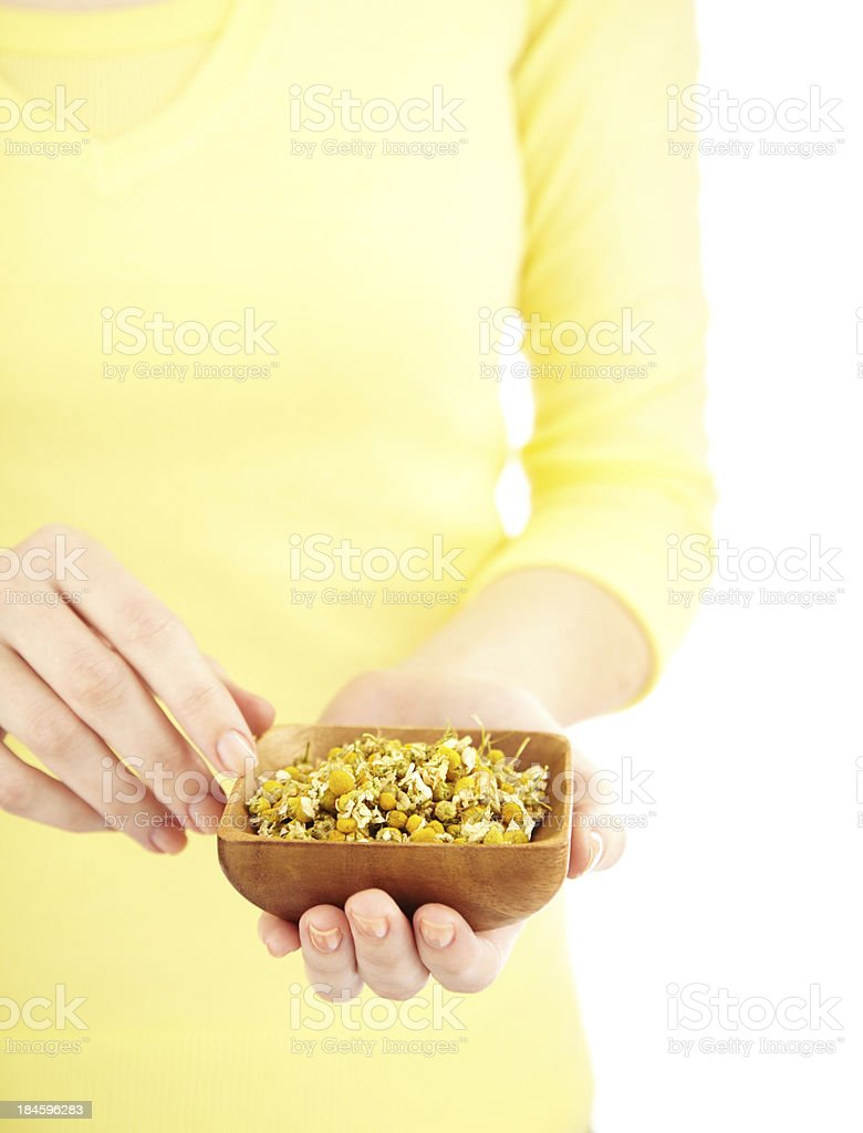 Mid section of a woman holding bowl with dried flowers royalty-free stock photo
