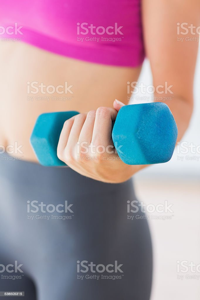 Mid section of a woman lifting dumbbell weight stock photo