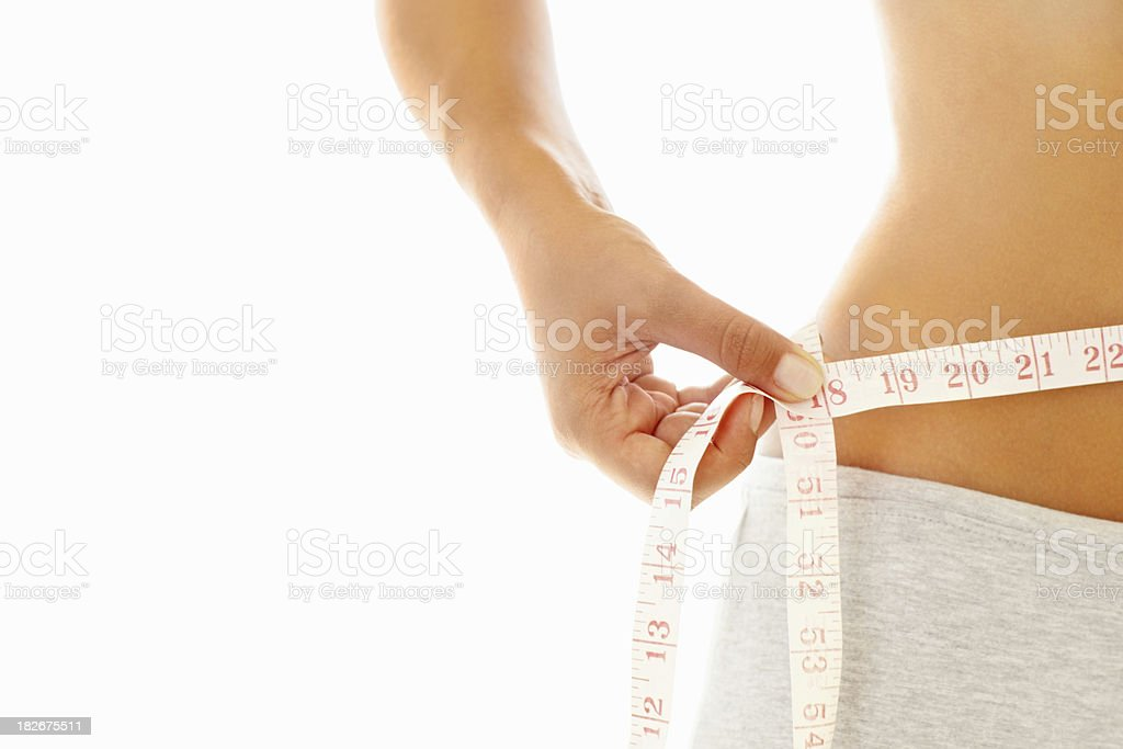 Mid section of a woman measuring her waist stock photo