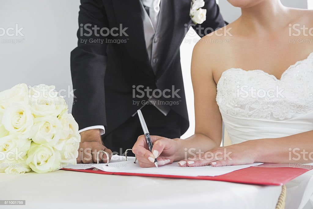 Mid section of a young couple signing wedding contract stock photo