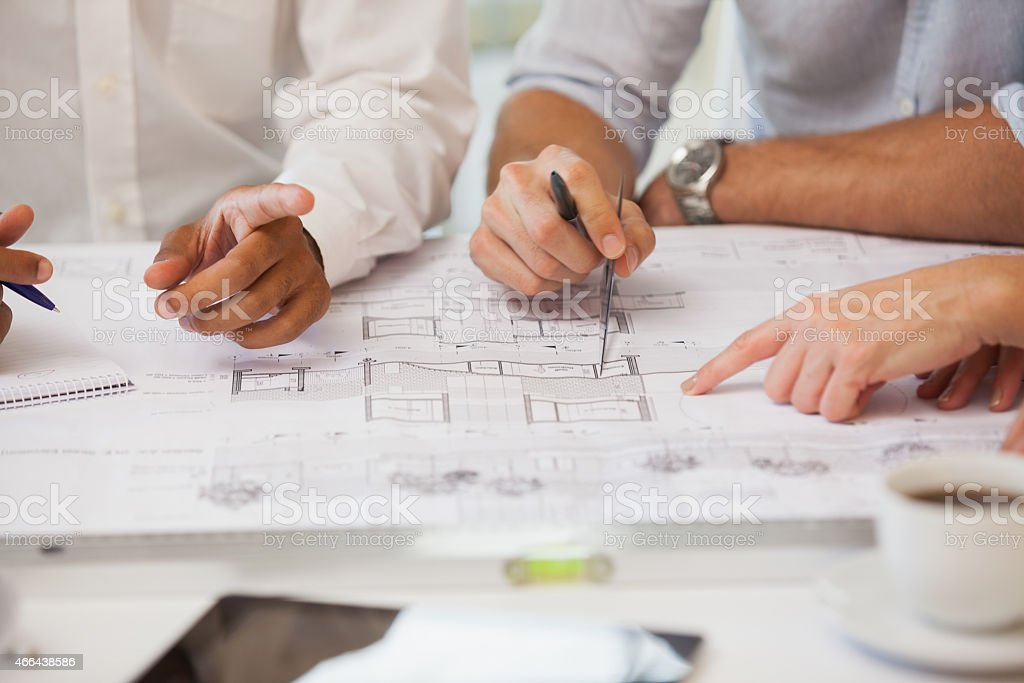 Mid section of business people working on blueprints stock photo