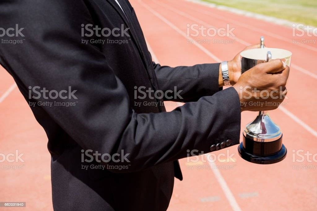 Mid section of businessman holding winning trophy stock photo