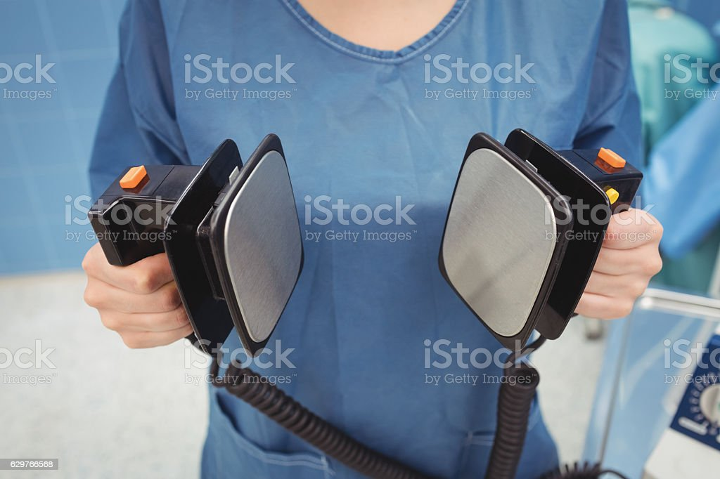 Mid section of female surgeon holding defibrillator stock photo
