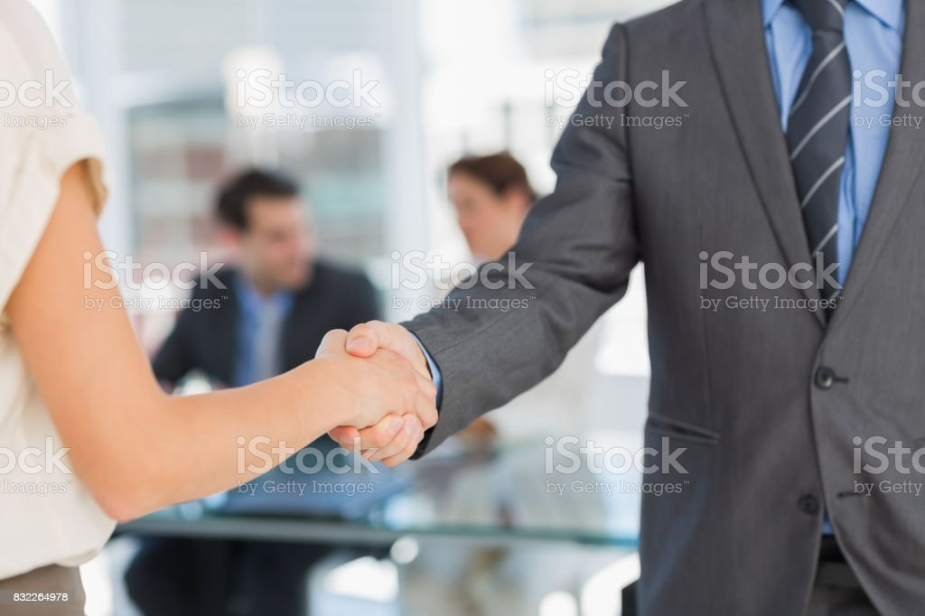 Mid section of handshake to seal a deal after meeting stock photo