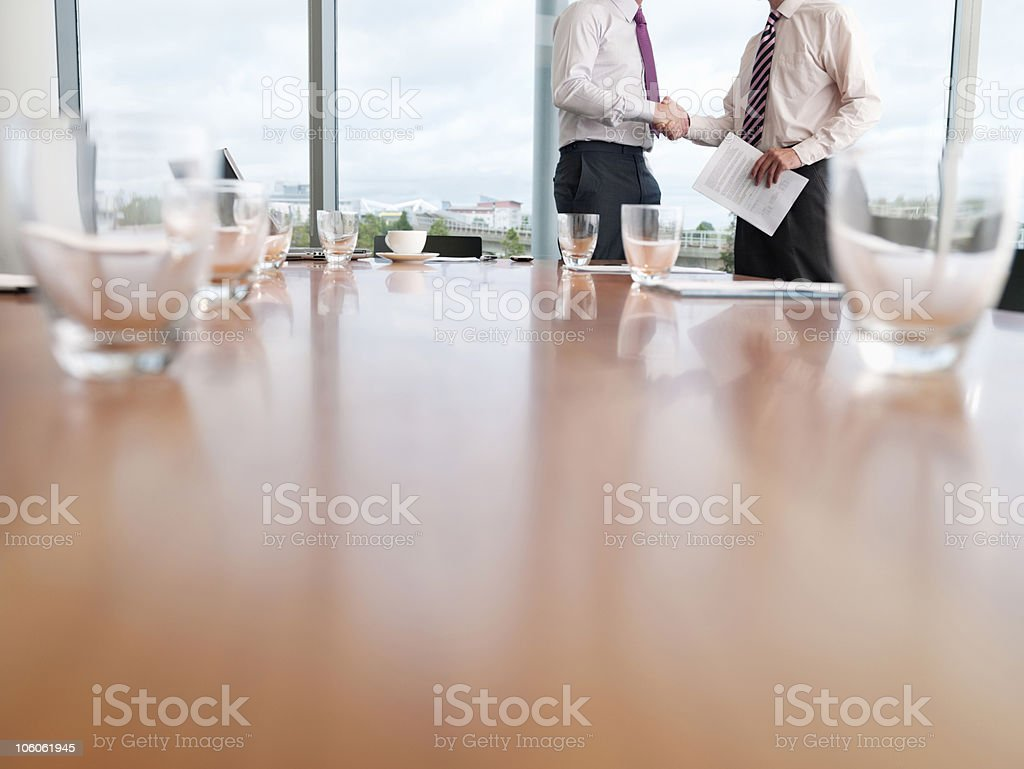 Mid section of two business men shaking hands after a deal royalty-free stock photo