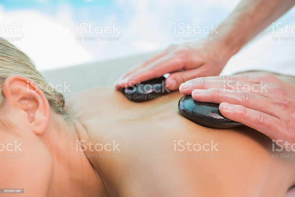 Mid section of woman receiving stone massage at health farm stock photo