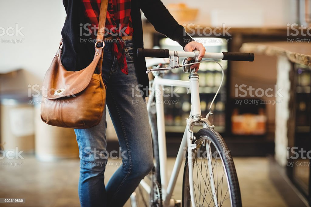 Mid section of woman standing along with bicycle stock photo