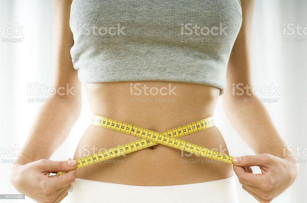 Mid section view of a young woman measuring her waist royalty-free stock photo