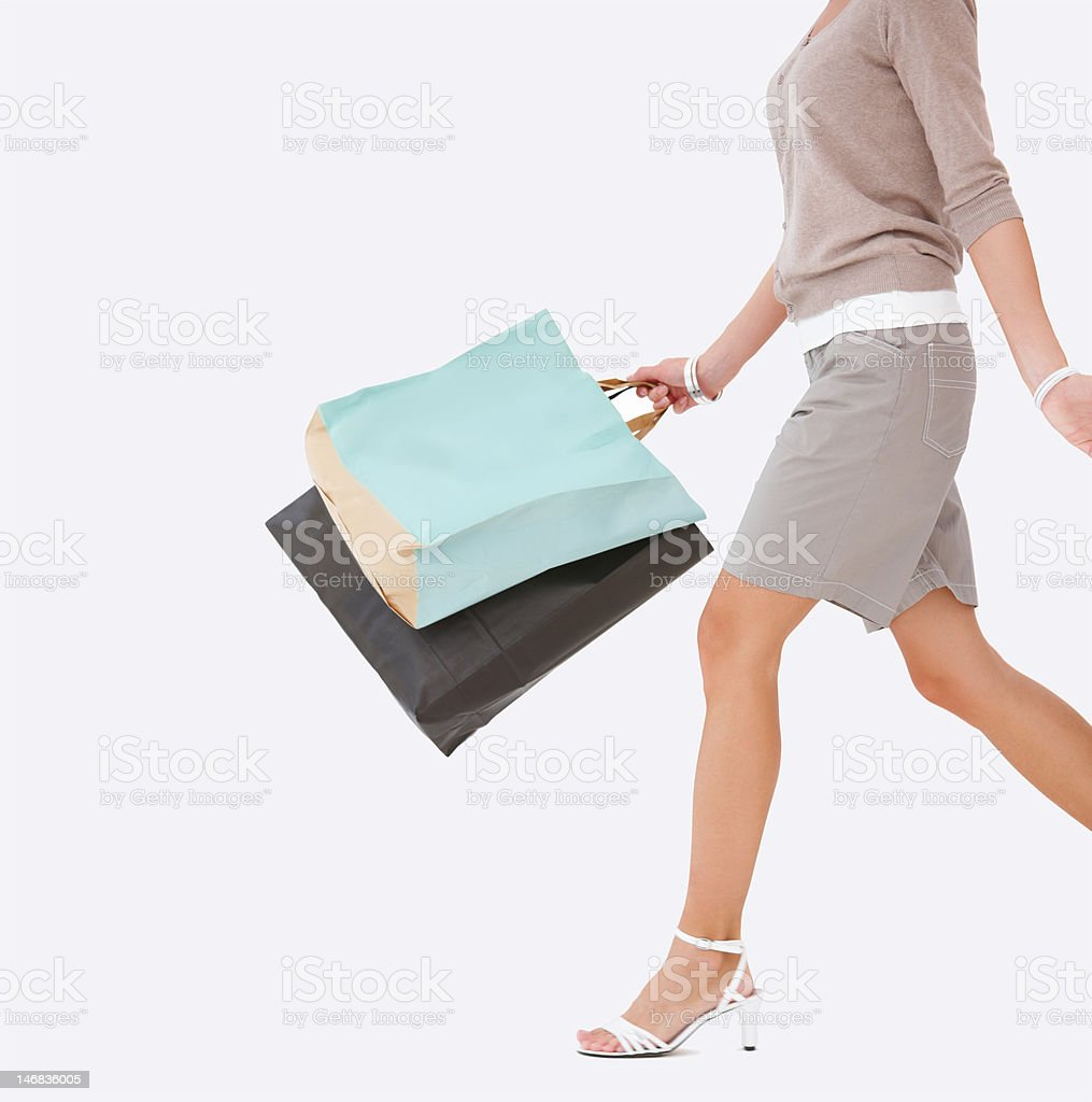 Mid section view of young woman walking with shopping bags royalty-free stock photo