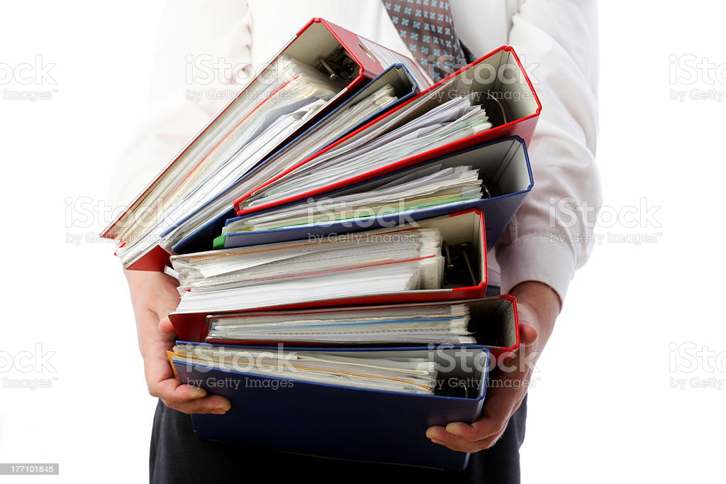 Mid view of a man holding a stack of colored binders royalty-free stock photo