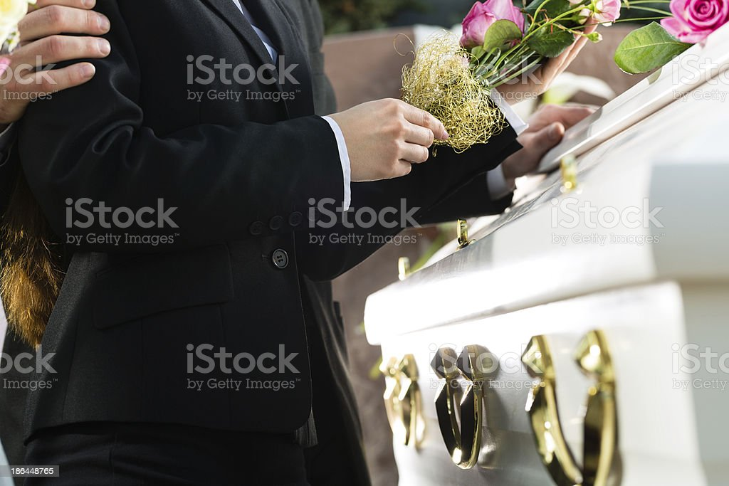 Mid view of a person with flowers at a coffin at a funeral stock photo