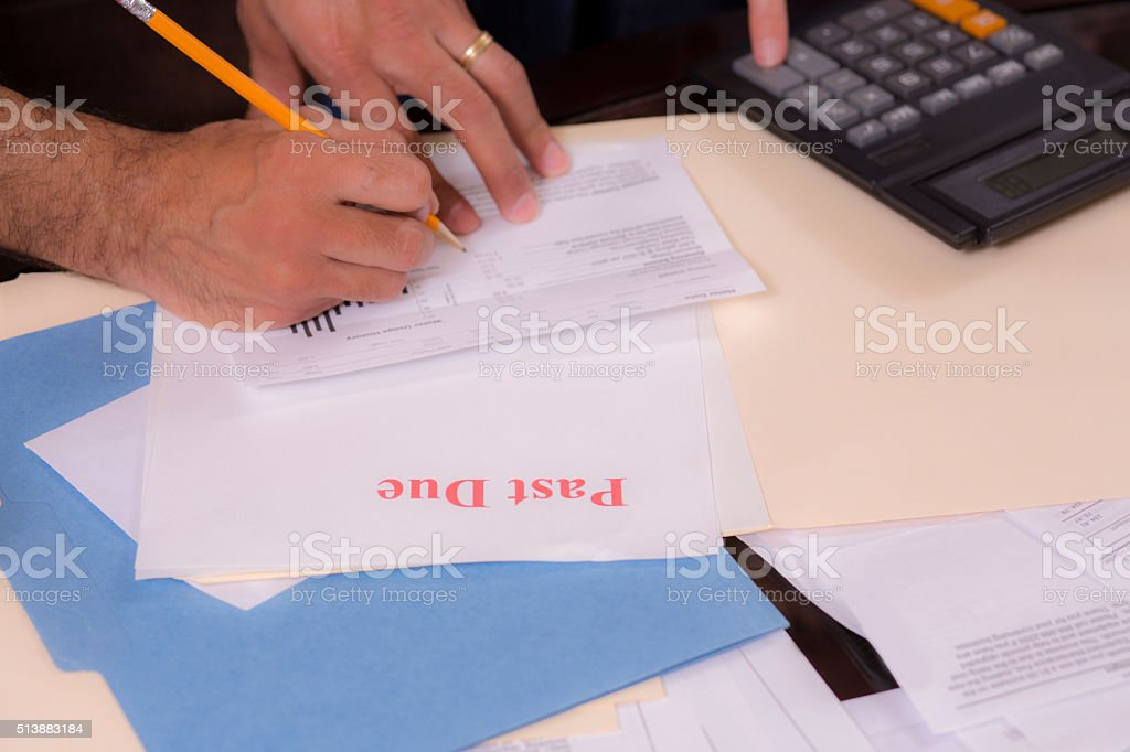 Mid-adult couple paying monthly bills at home. stock photo