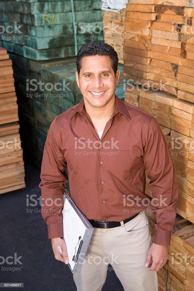 Mid-adult man stock-taking in warehouse stock photo