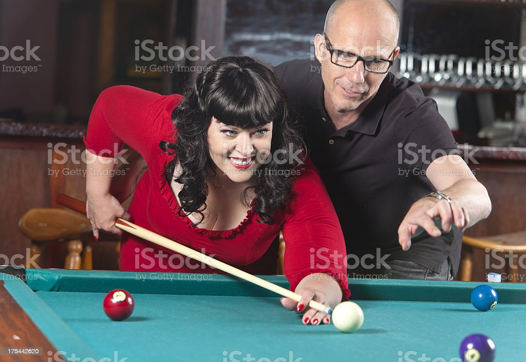 Midadult man teaching young woman how to play billiards stock photo