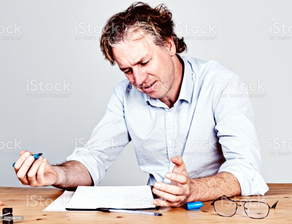 Mid-adult man, working at desk,  looks down, frowning and gesturing stock photo
