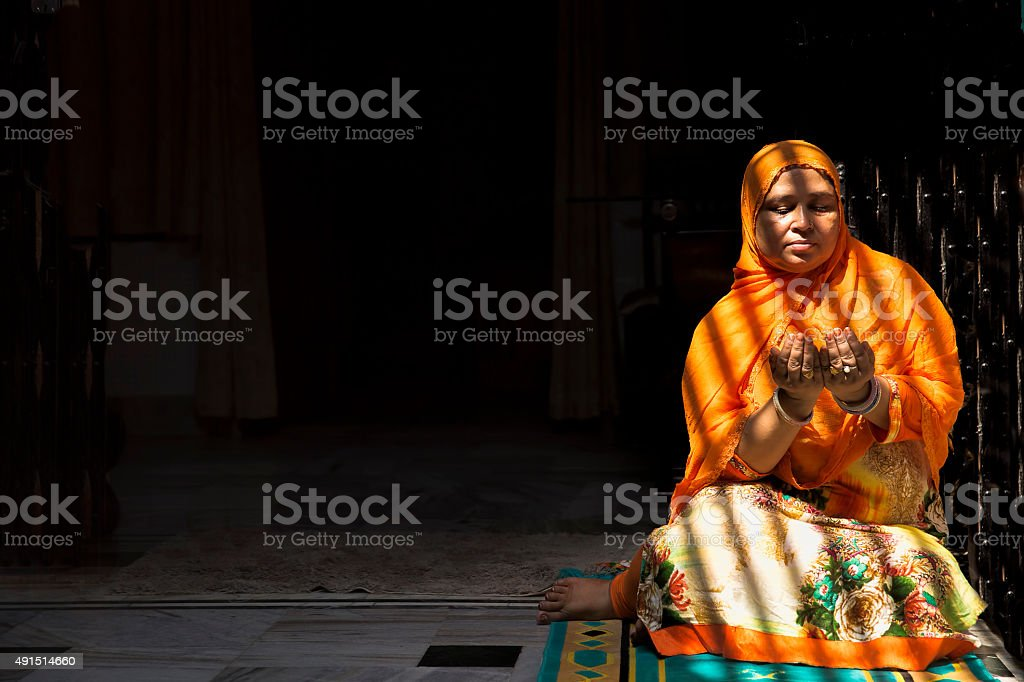 Mid-Adult Muslim Woman praying, with folded hands stock photo
