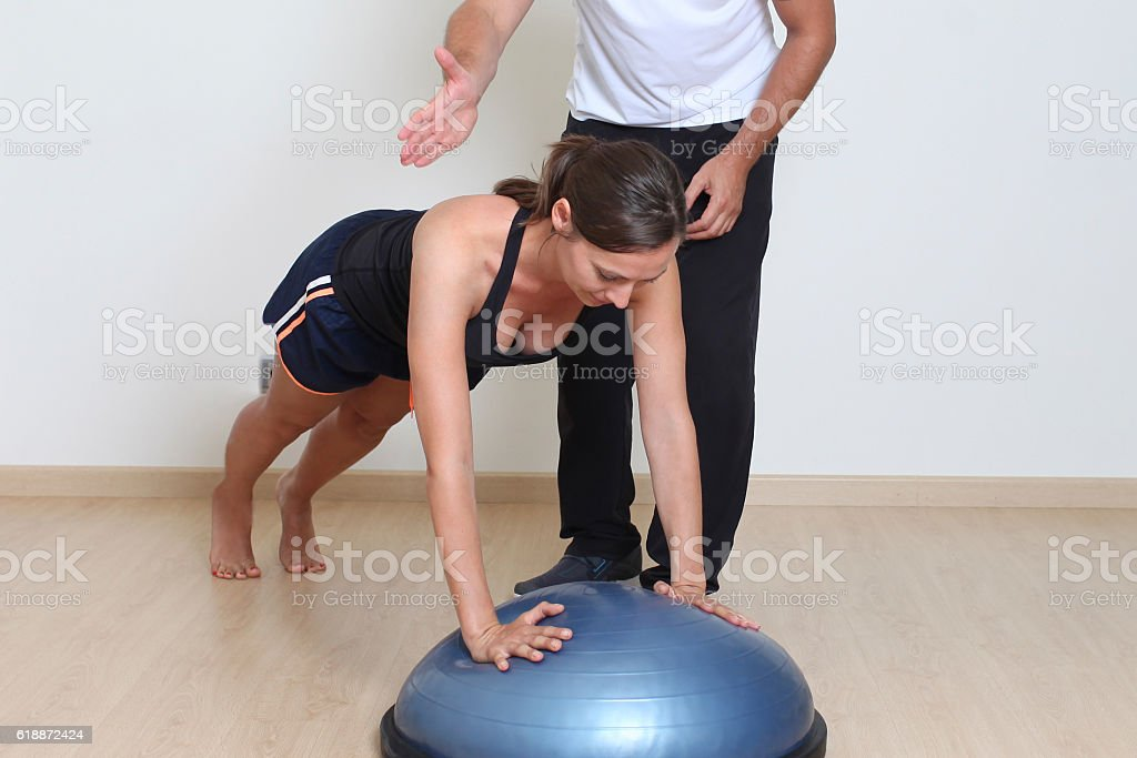 Mid-adult woman exercising with personal trainer stock photo