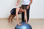 Mid-adult woman exercising with personal trainer