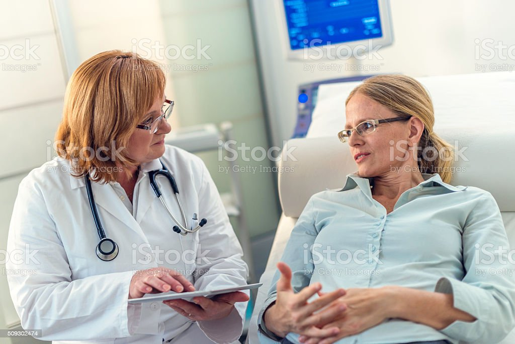 Mid-adult woman explaining her problems to her doctor stock photo