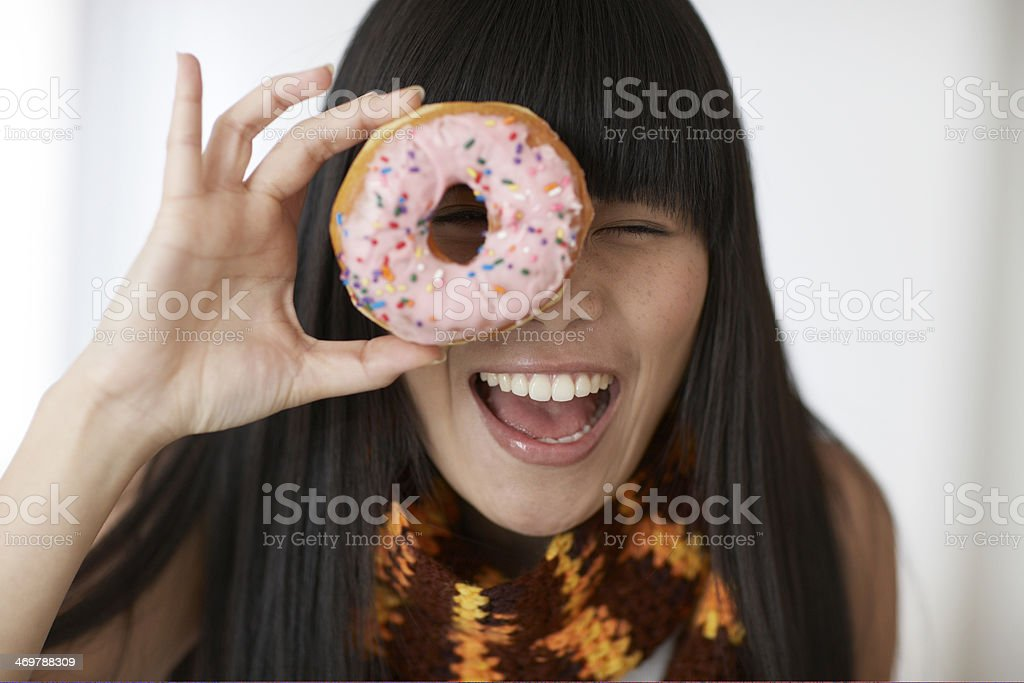 Mid-Adult Woman Looking Through Donut stock photo