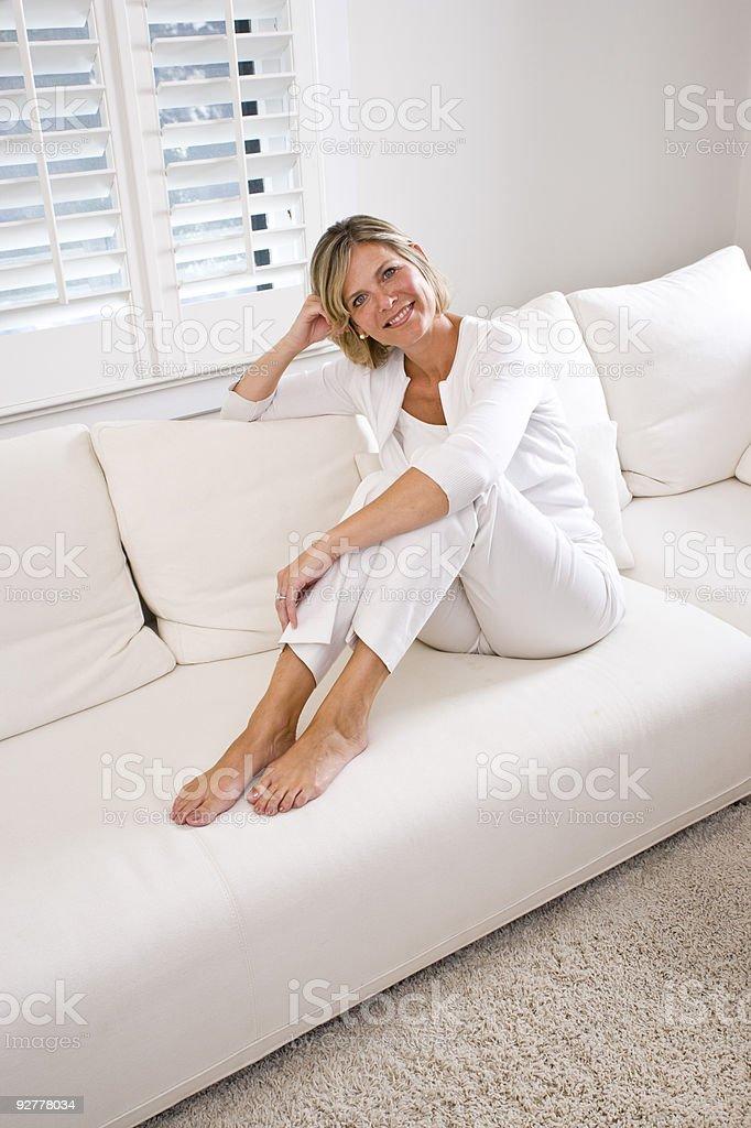 Media edad mujer sentada en un sofá de la sala de estar foto de stock libre de derechos