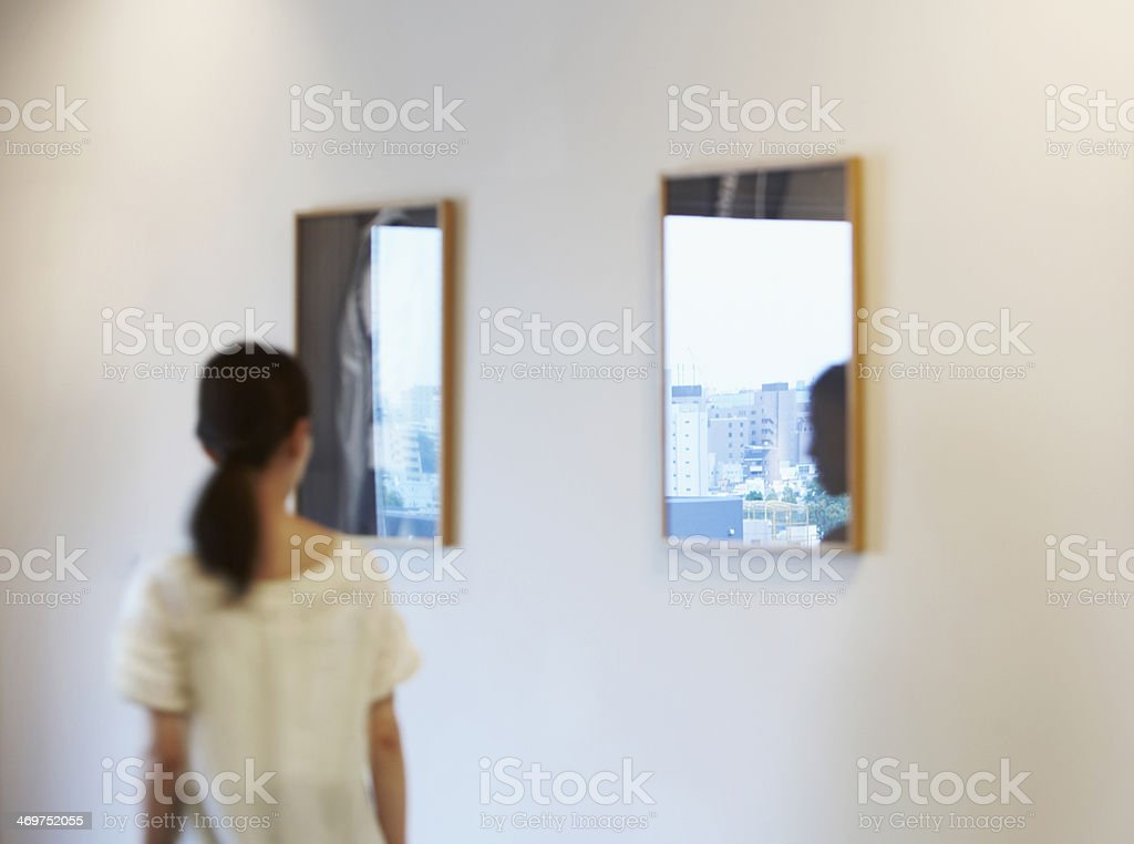 Mid-Adult Woman Walking by Wall Mirrors stock photo