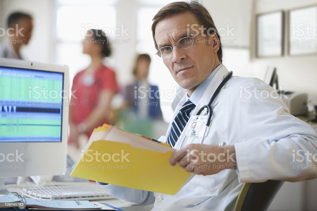 Mid-age doctor looking at the camera holding a folder with records stock photo